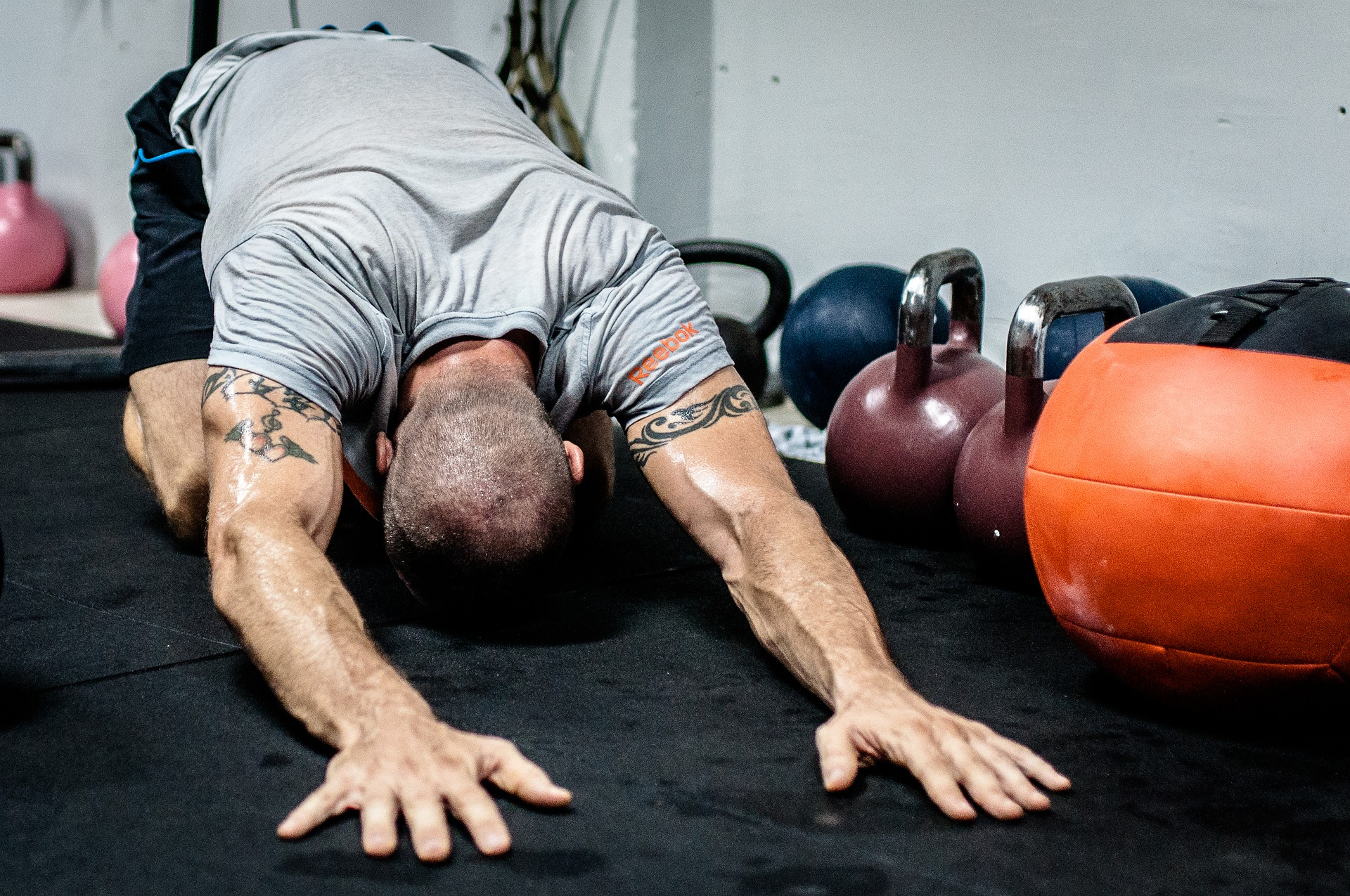 Man doing one of the CrossFit Stretches on the box floor next to kettlebells